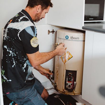 Plumbers Nerang plumber repairing a Hot Water System